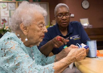 Resident and caretaker doing crafts