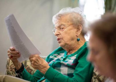 senior resident reading with group