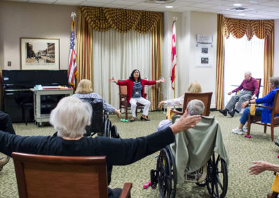 Caregiver leading activity at senior living facility