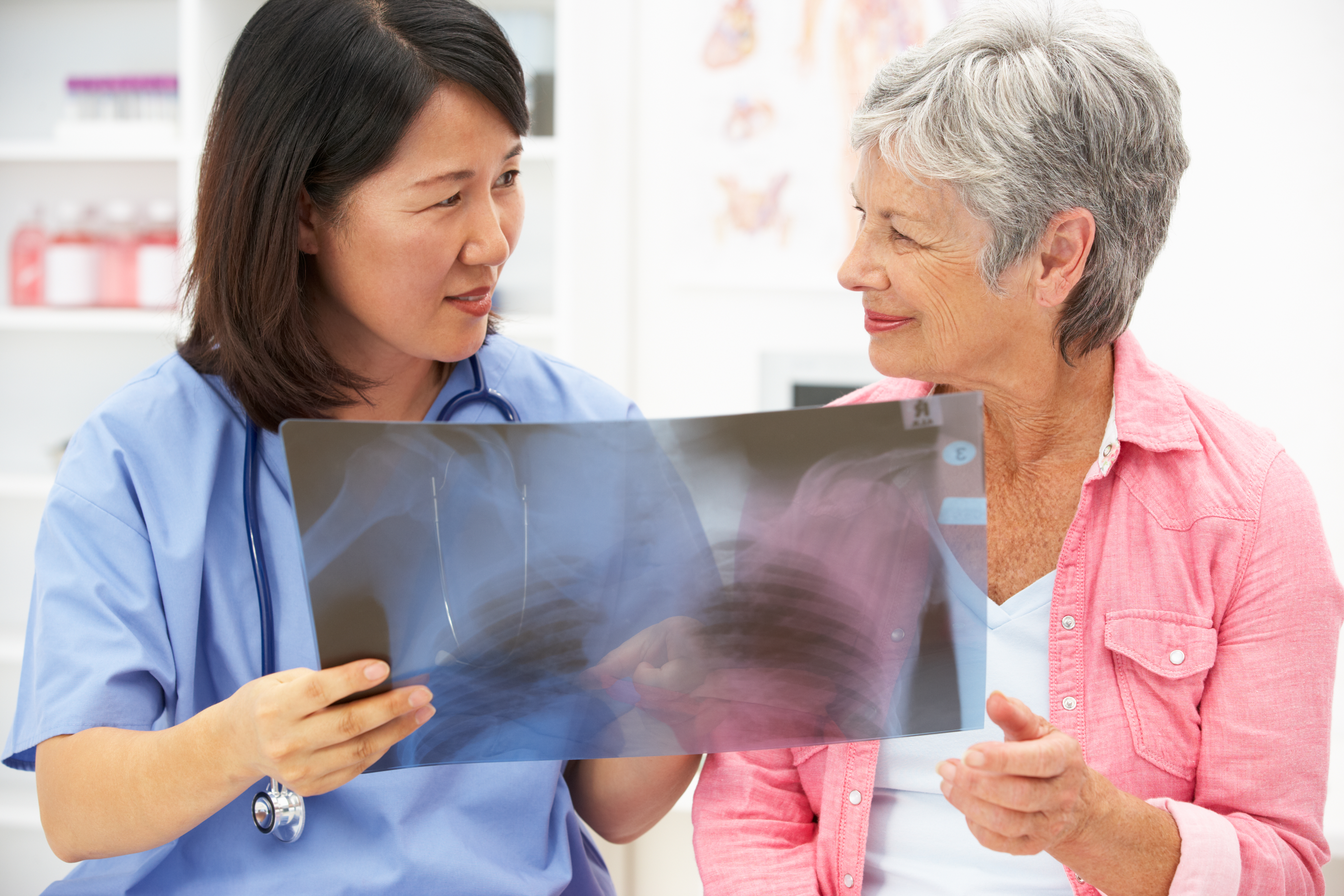 nurse looking at x-ray with senior woman