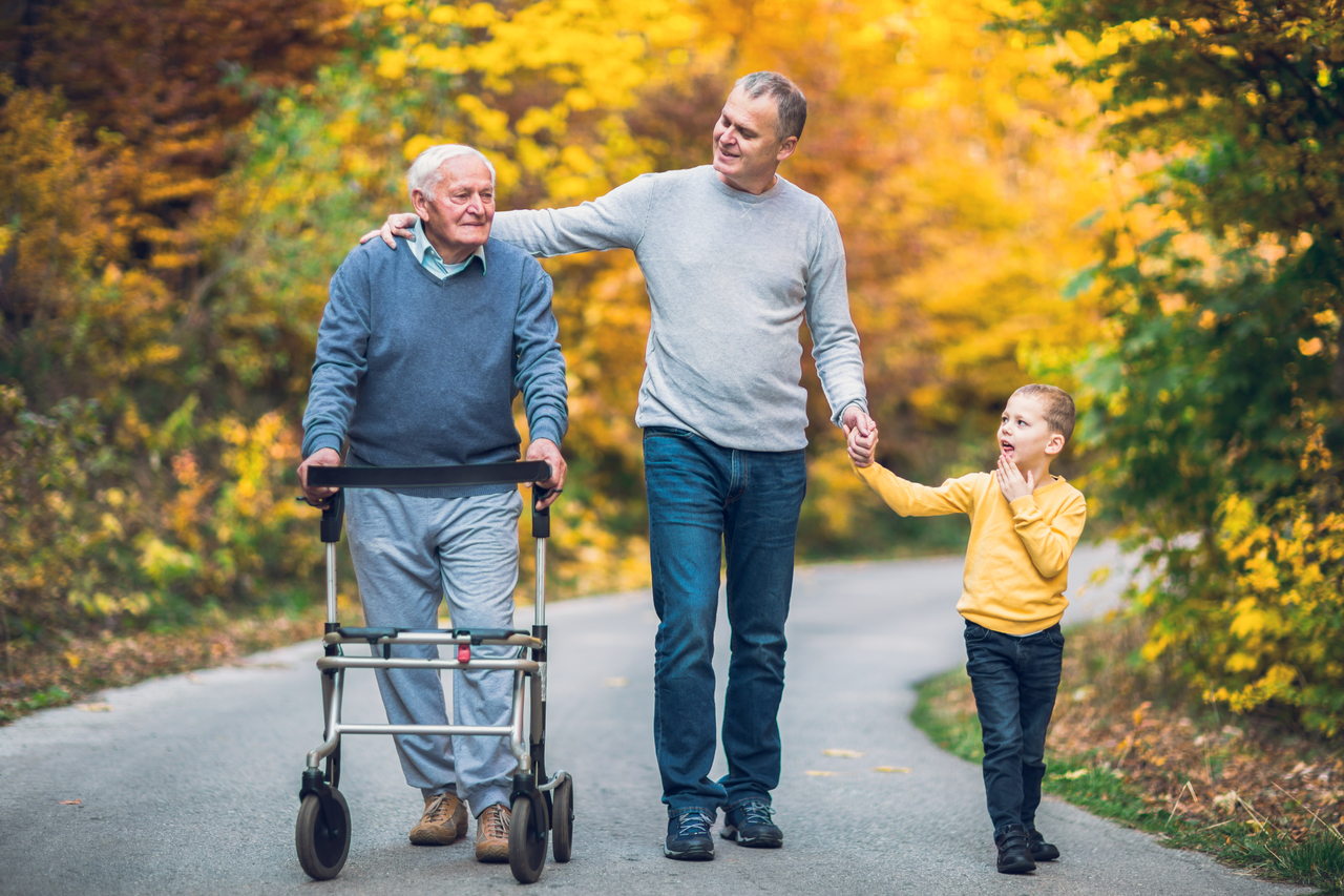 family walks with senior in a walker