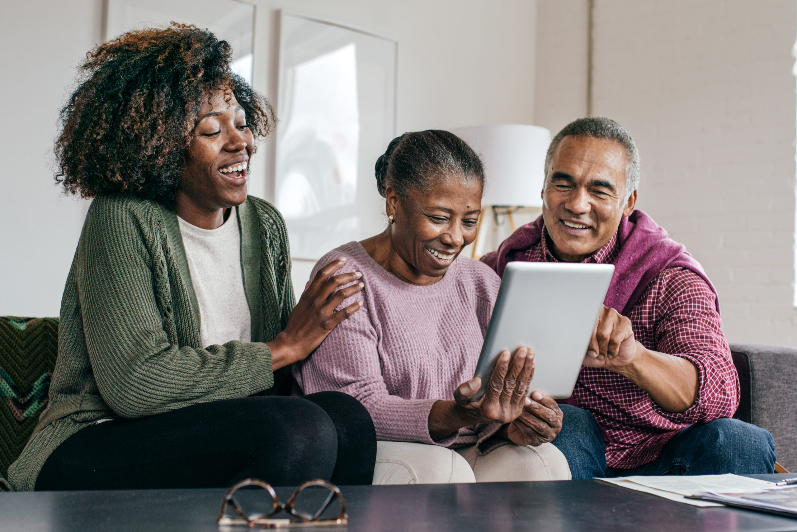 senior couple and daughter looking at an ipad
