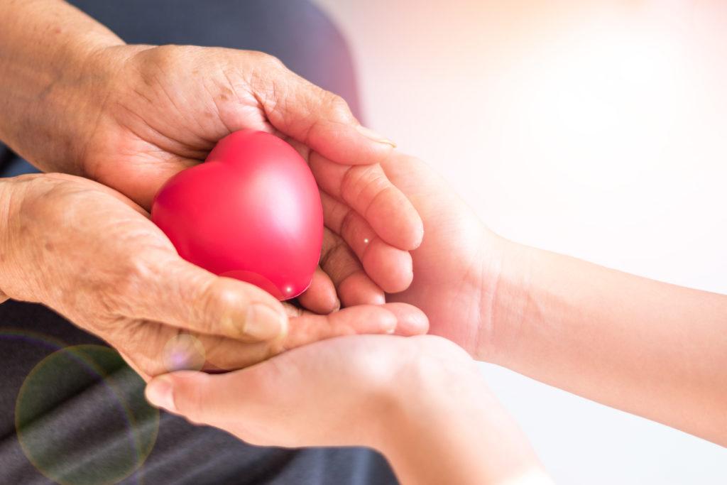 senior and caregiver holding a heart stress ball