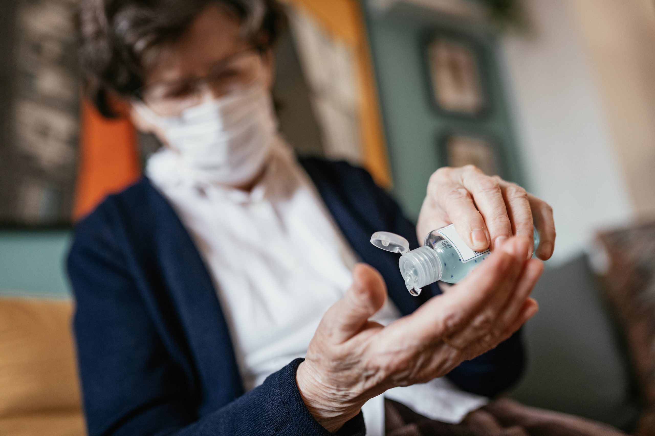 Senior woman applying hand sanitizer at home