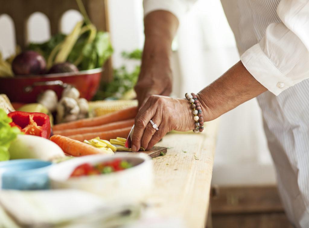 elderly woman chopping vegetables