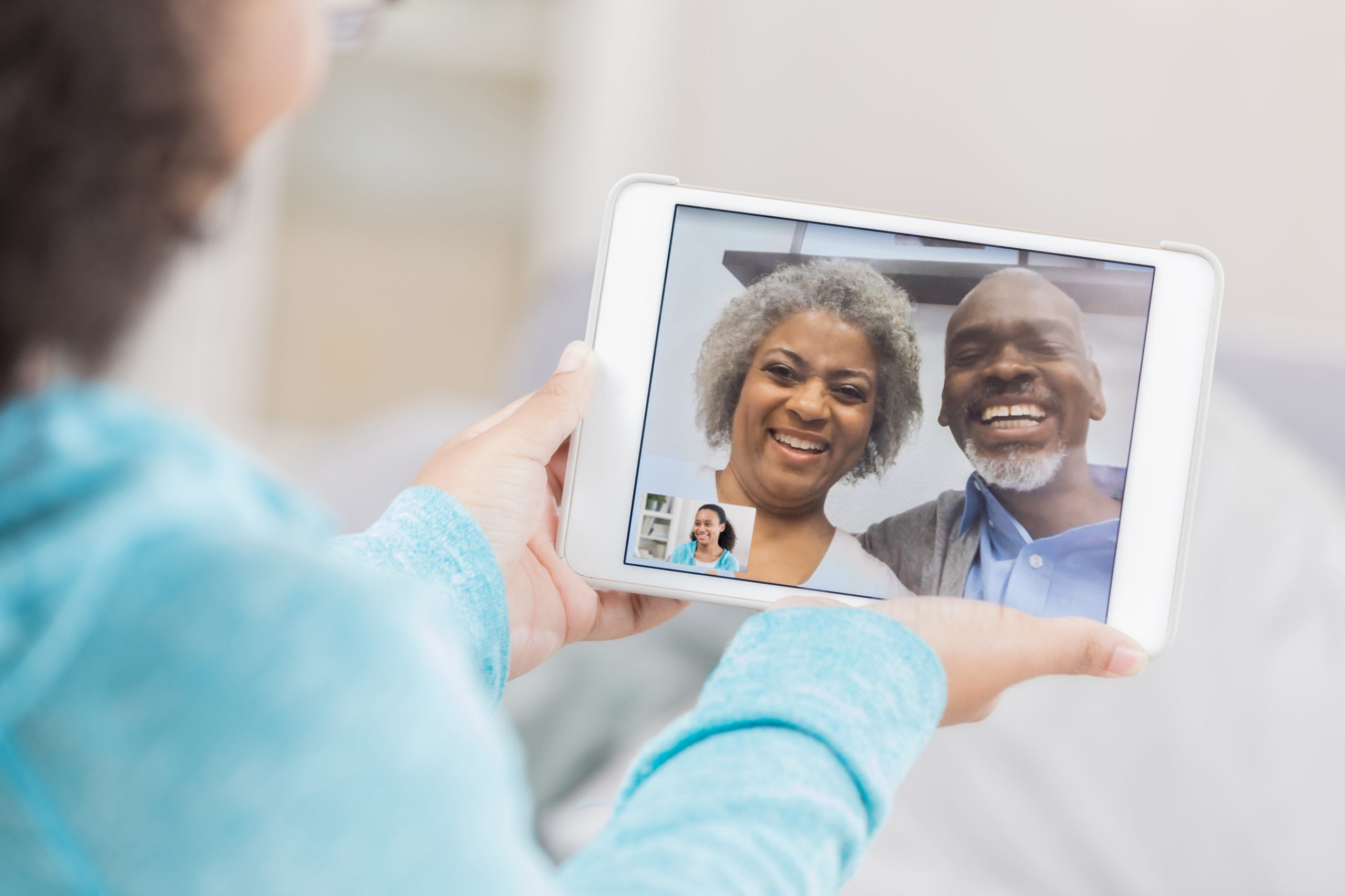 Senior couple video chatting on granddaughter's device screen