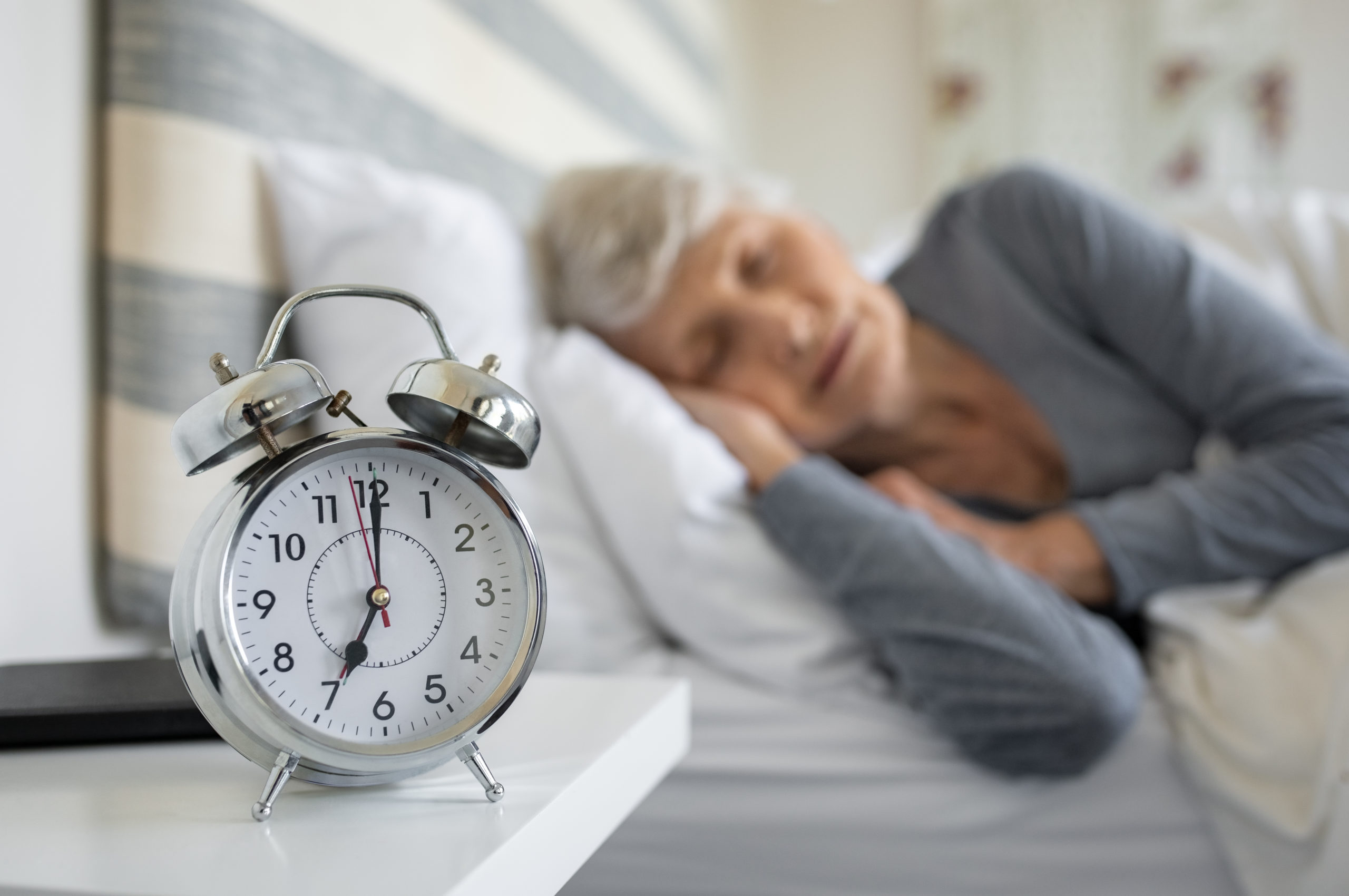 senior woman sleeping with close-up of alarm clock