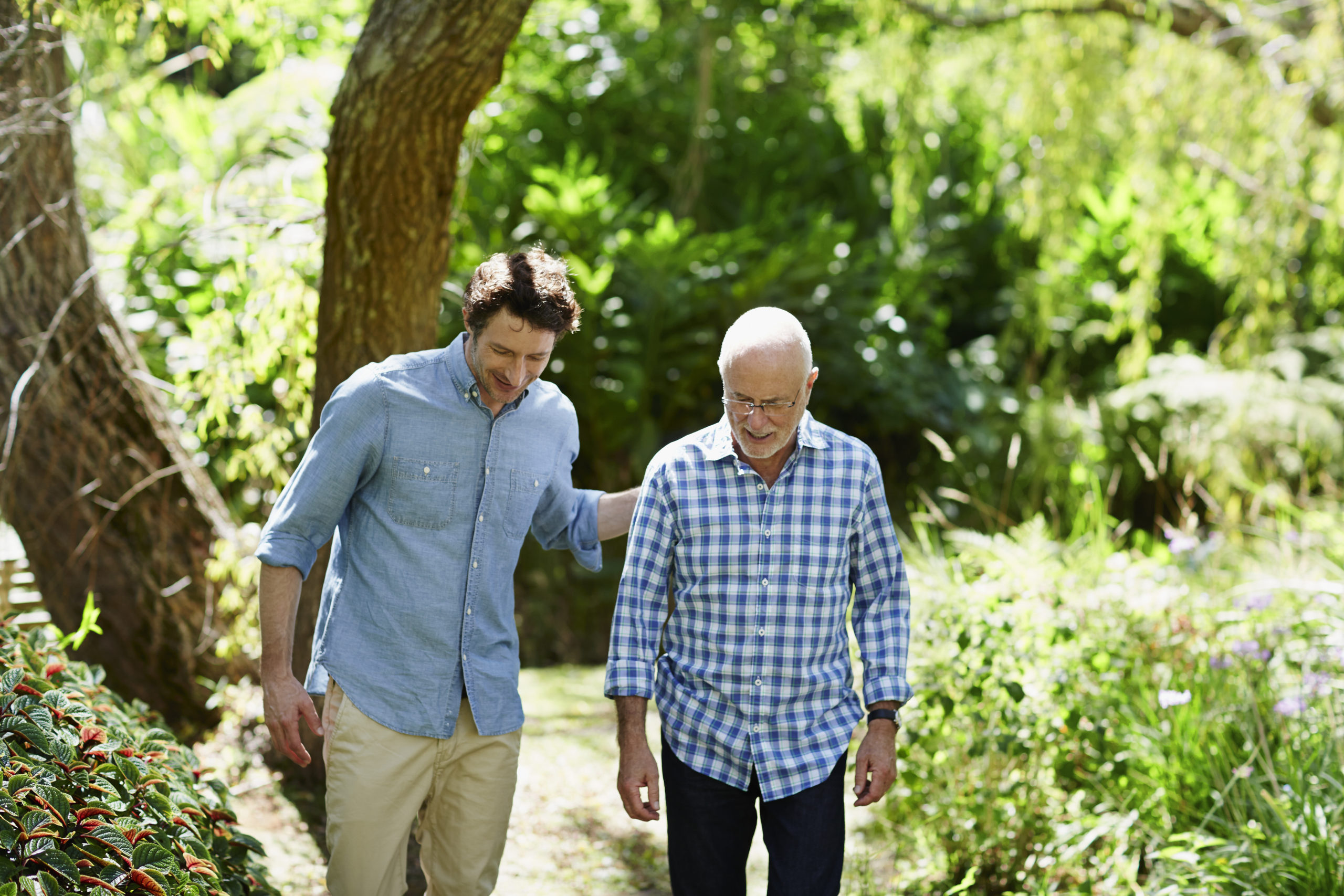 Son walking outdoors with senior male