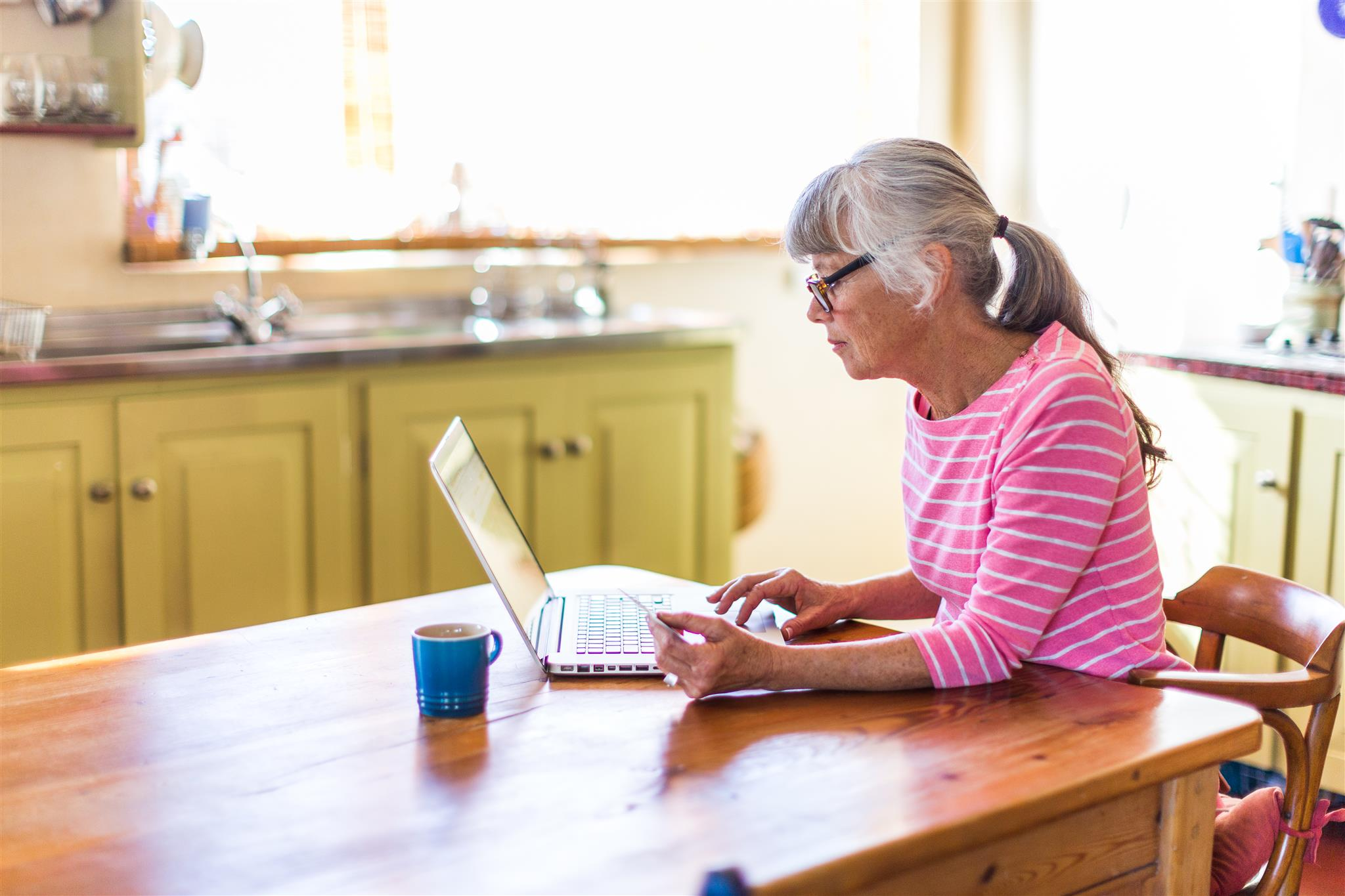senior female browses online in her kitchen