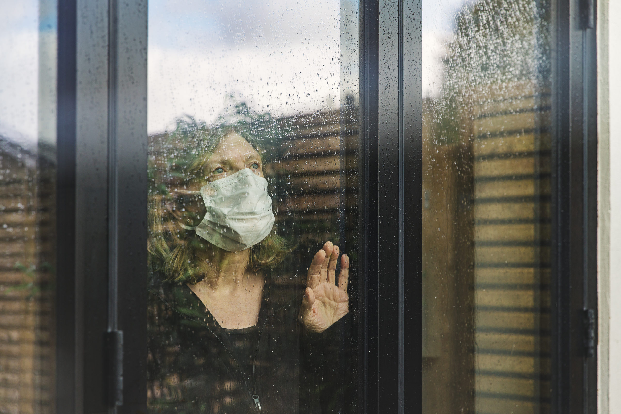 Senior woman with mask looking out window