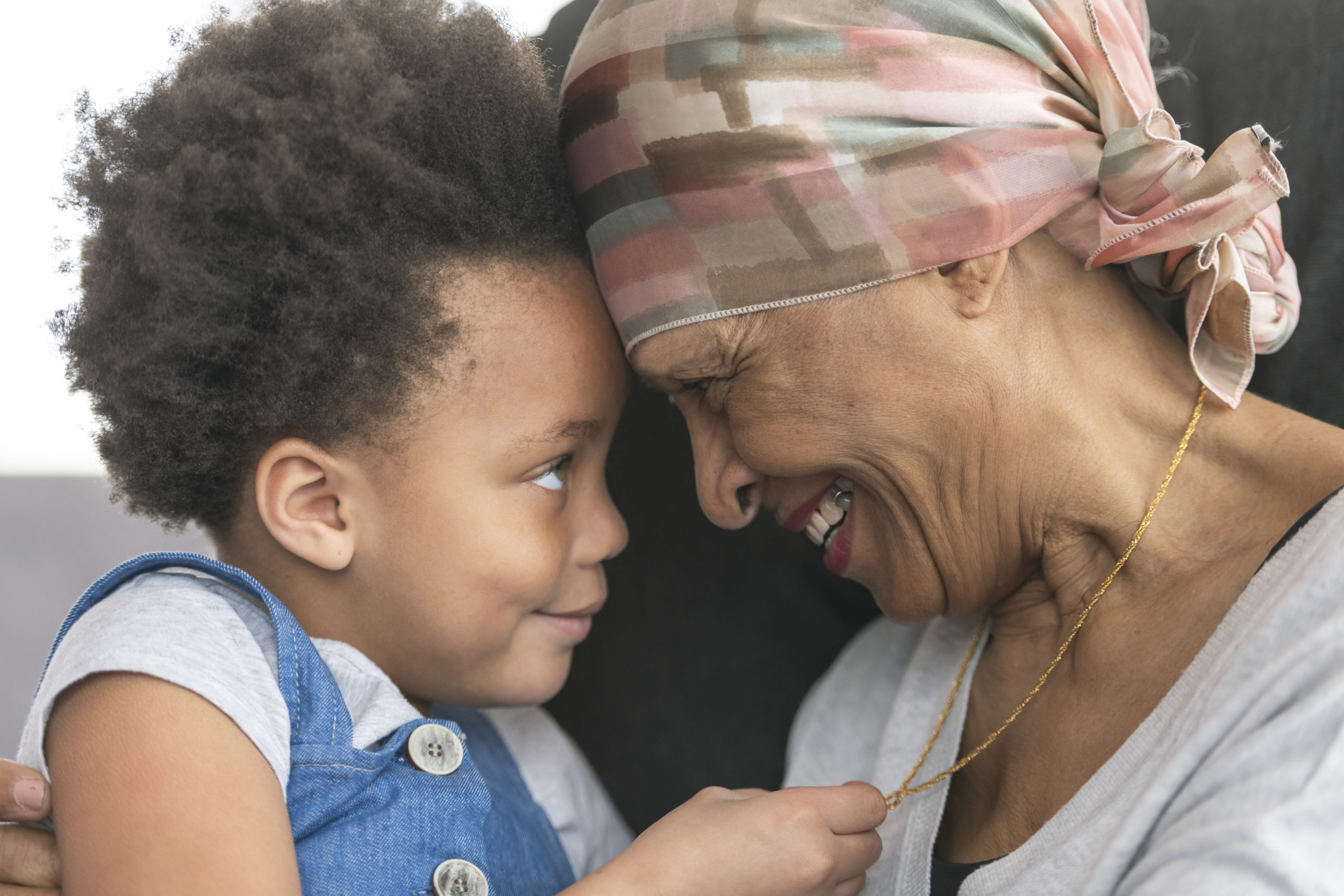 Senior woman with cancer lovingly holds granddaughter