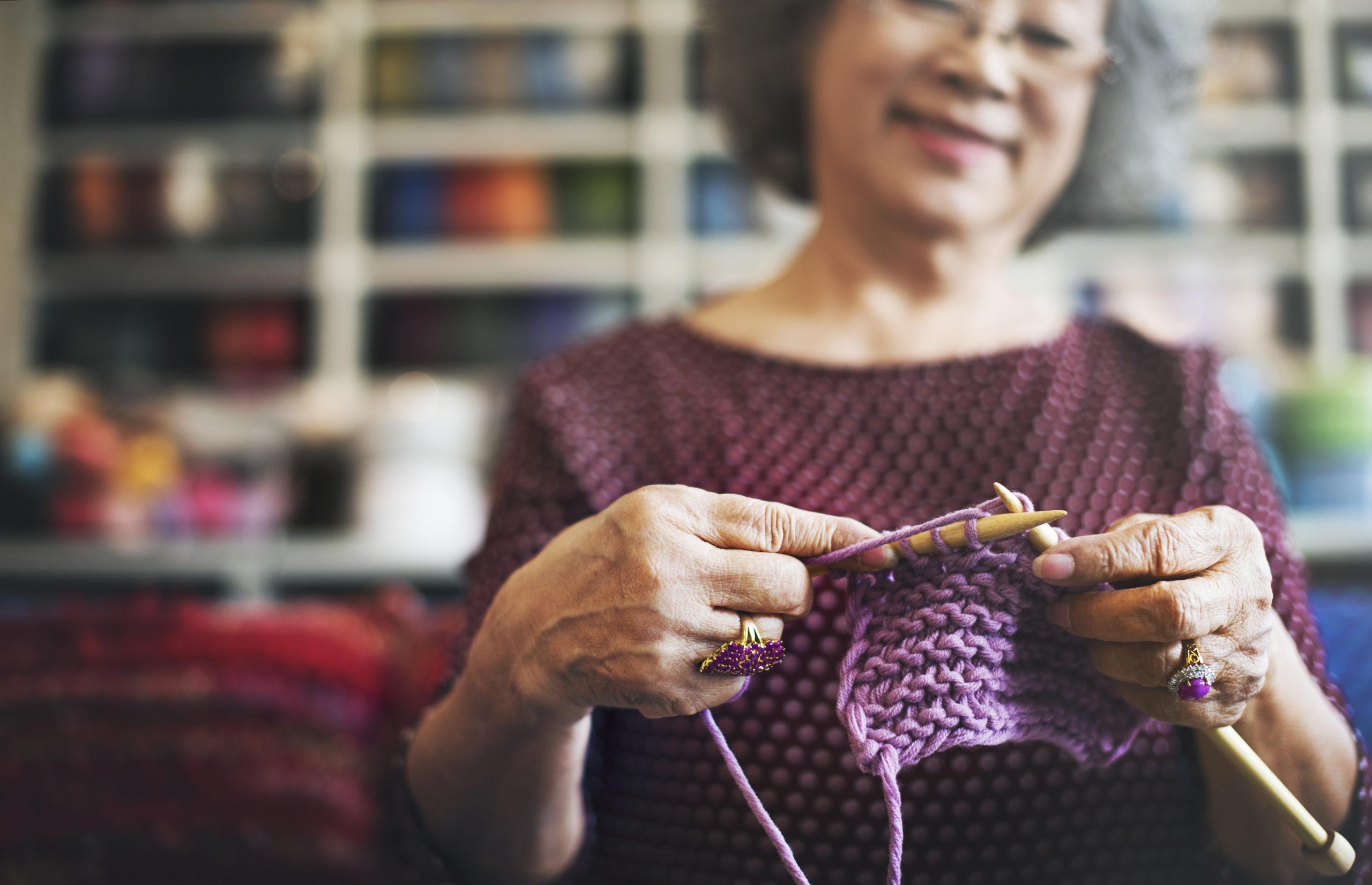 senior woman knitting a scarf