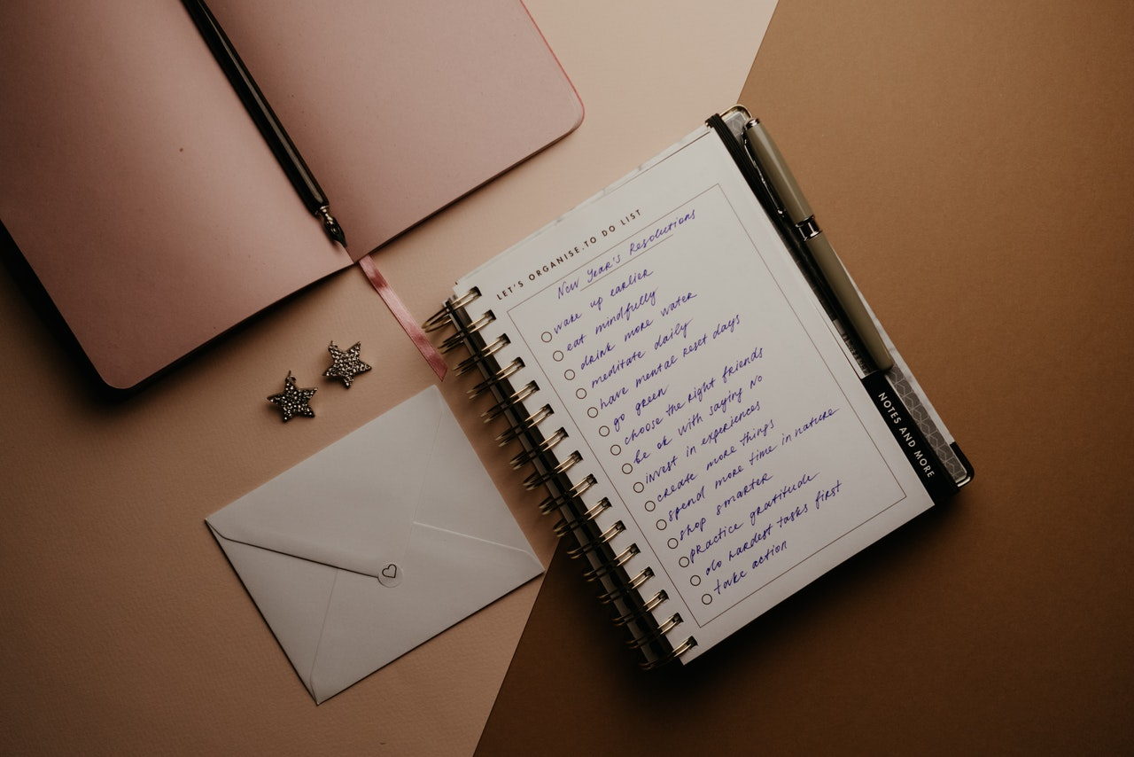 A notebook and a journal on a table with New Year's Resolutions and Goal Setting