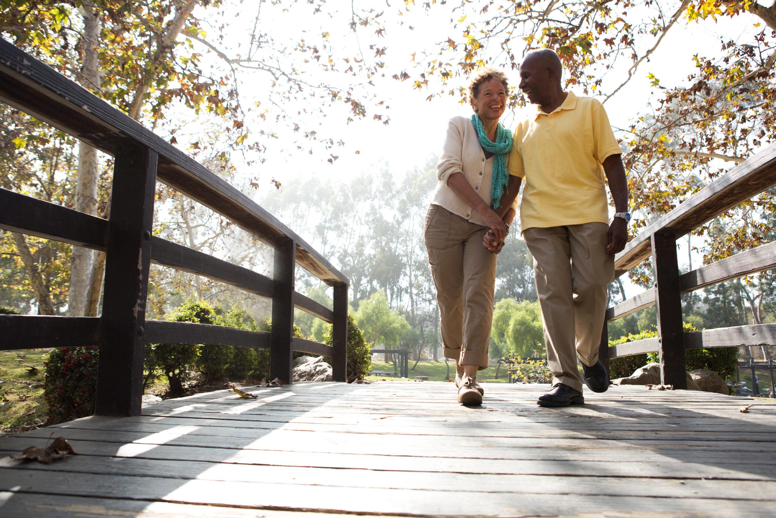 senior couple walking over a bridge