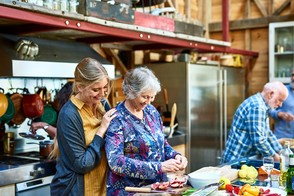 Two cheerful women preparing food on kitchen work surface, smiling, fresh ingredients, togetherness